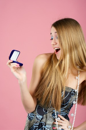 admired: Beautiful young woman is surprised by an engagement ring in the opened gift box