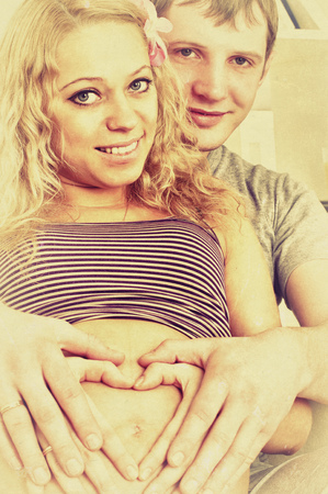 tammy: Vintage style photo with portrait of beautiful young pregnant couple where hands making a heart shape on the pregnant womans belly. Stock Photo