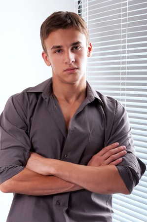 Handsome young man with crossed arms standing near venetian blind in the office photo