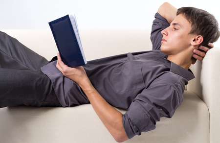 Young man reading book while lying at the couch photo