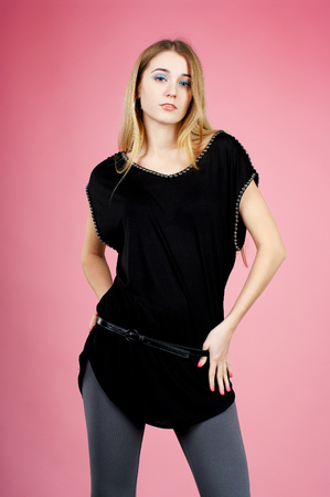 pink posing: Young blond lady in black dress posing on pink background