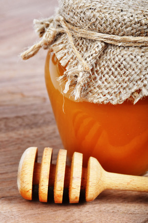 drizzler: Sweet honey in a jar with a drizzler on a wooden board Stock Photo