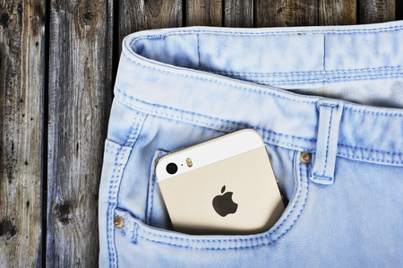 5s: CHLUMCANY, CZECH REPUBLIC, MARCH 10, 2015: Apple iPhone 5s in a blue denim pocket on a wooden background