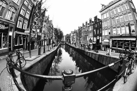 AMSTERDAM, NETHERLANDS, MARCH 16, 2013: Black and white photography of Amsterdam street with a river taken from a bridge with fish-eye lens Editorial
