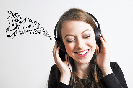 listen music: Young girl listening to a music with music notes going out from her headphones