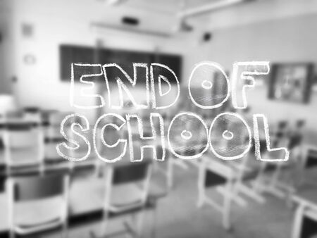 edu: A chalk lettering with a blurred classroom in the background - black and white photography.