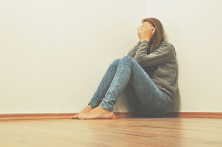 femme triste: Sad girl cacher dans le coin à la maison Banque d'images