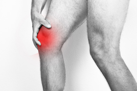 soreness: Man holding his knee because of a pain.