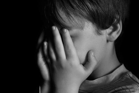 maltrato infantil: Niño llorando en la oscuridad Foto de archivo