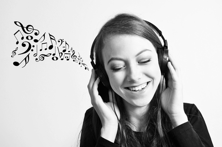 Young girl listening to a music with music notes going out from her headphones