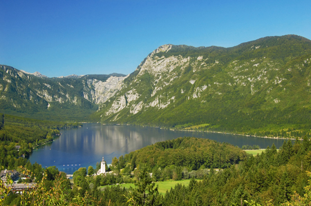 Breathtaking view of the famous Bohinj lake from above. Beautiful view ot the Triglav mountains, Triglav national park, and the church of St John the Baptist,.Slovenia, Europe Stock Photo