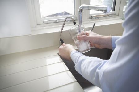 モダンなキッチンの水フィルターから冷たい水のガラスを注ぐ男性