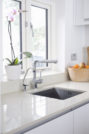 sink drain: Modern kitchen sink and tap inset into stone  quartz worktop