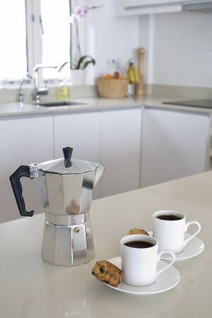 stone worktop: cafetiere and coffee cups on breakfast bar in modern clean composition