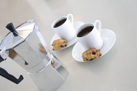 cafetiere and coffee cups on breakfast bar in modern clean composition