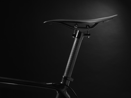 shot of a modern racing bikes seat and section of frame. Lit very moodily with only certain sections visible too create a stealthy look. The graduated background has been achieved with lighting and does not include any post production adjustments. There i Stock Photo
