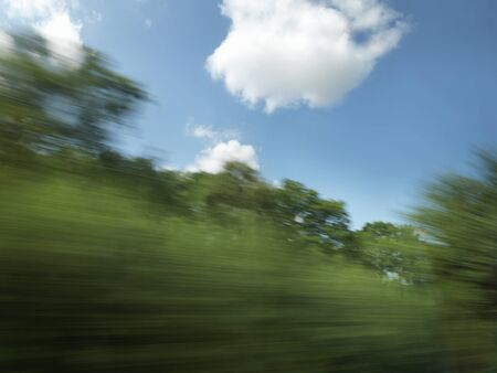 Shot from a window of a fast moving train of blurred trees and countryside with blue sky on a bright summers day. Stock Photo