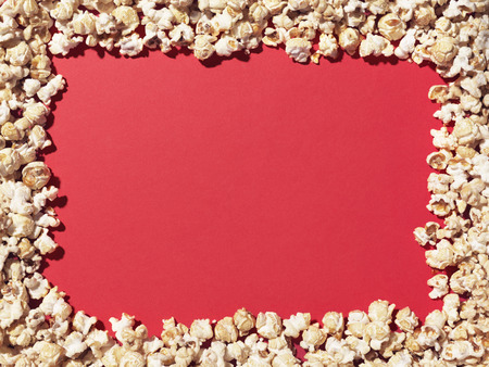 Shot of popcorn arranged to give a border to a plain, red area ideal for designer to add copy. Stock Photo