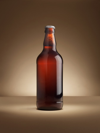 shot of a single bottle of real ale on a coloured background lit with in a halo, vignette style