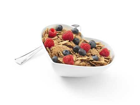 Angled shot of a heart shaped bowl of cereal with bran flakes covered in raspberries and blueberries on a pure white background