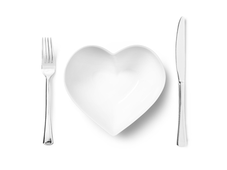 Shot of a heart shaped plate or bowl with a silver knife and fork Stock Photo