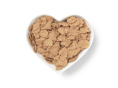 shot of a heart shaped cereal bowl full of bran flakes cut out on a white background