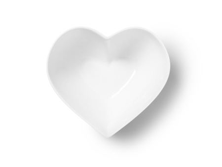 Straight down, birds eye shot of an empty heart shaped bowl or plate on a pure white background