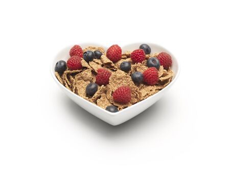 simple shot of bran flakes cereal with blueberries and strawberries added on a pure white background