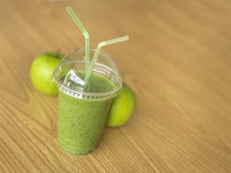 緑のショットを閉じる、バック グラウンドでリンゴを持つテーブルでスムージーを奪います。 写真素材