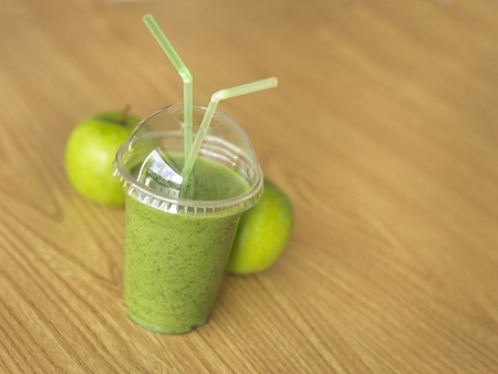 Close up shot of a green, take away, smoothie on a table with apples in the background.