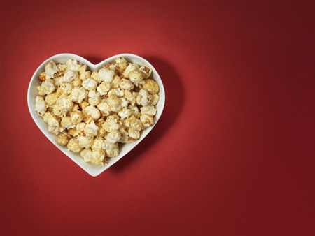 shot of cinema style popcorn in a heart shaped bowl on a bright red background