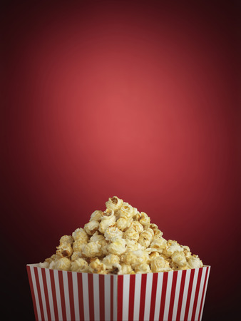 Shot of cinema style popcorn in a traditional striped box on a red background