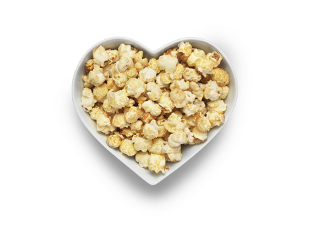 popcorn bowls: Shot of cinema style popcorn in a heart shaped bowl isolated on a white background Stock Photo