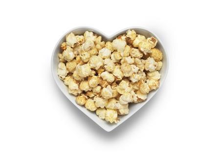 palomitas: Tiro de palomitas de maíz de un cine en un tazón en forma de corazón aislado en un fondo blanco
