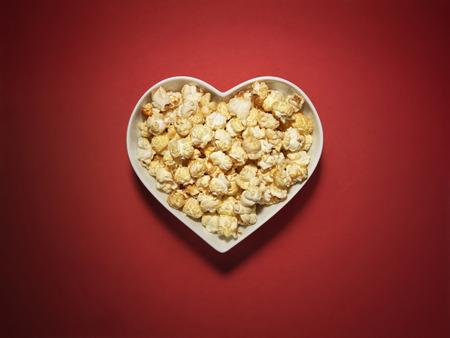 心の中の映画スタイルのポップコーンのショット形活気に満ちた、明るい赤の背景にボウル 写真素材