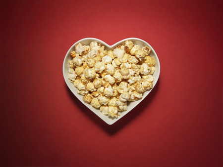 Shot of cinema style popcorn in a heart shaped bowl on a vibrant and bright red background Stock Photo