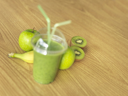 Shot of a green, take away, smoothie on a wooden table with selective focus on fruit in background. Zdjęcie Seryjne