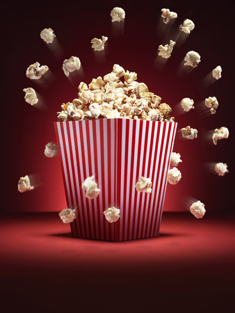 Shot of cinema style popcorn in a traditional box with pieces flying out