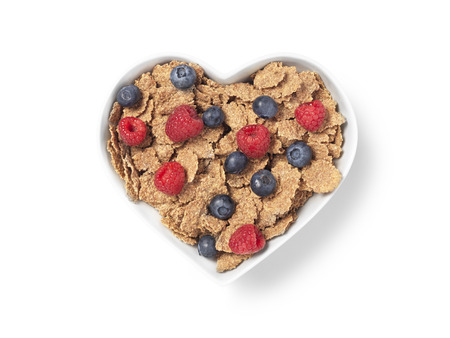 Shot of a heart shaped bowl of bran cereal with raspberries and blueberries implying healthy eating and lifestyle. The image has a clipping path and copy space for the designer.