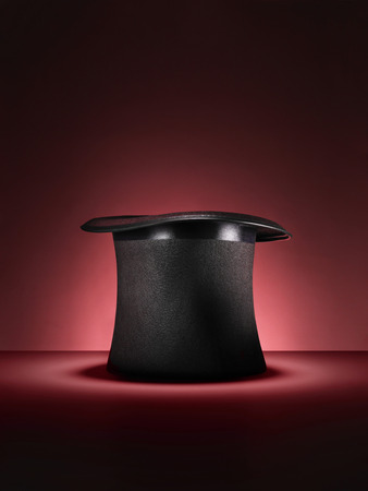 Shot of a traditional magicians style top hat set up for a trick or illusion on a red background