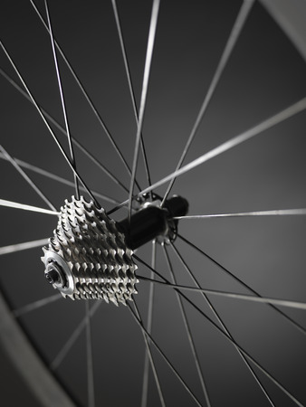 close up shot of bicycle wheel showing gears or cogs with a shallow depth of field showing spokes and rim. The shot has bee taken in the studio and has a monochrome feel due to metal and carbon in the pic.