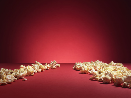 shot of cinema style popcorn on a red background with spotlight and copy space.