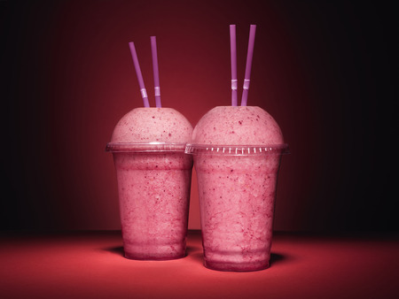 shot of a pair of pink, fruit, berry smoothies on a vibrant red background with copy space Stock Photo