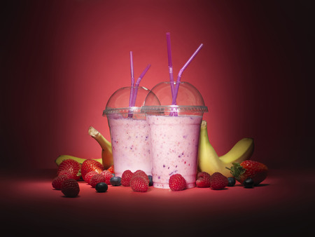 Shot of two take away smoothies in plastic cups on a red background with an array of different summer fruits