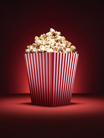 Shot of a traditional box of cinema style popcorn with spotlighting on a vibrant red background with copy space Stock Photo