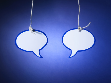 Shot of two cut out speech bubbles, one sharp one soft in the distance on a blue background