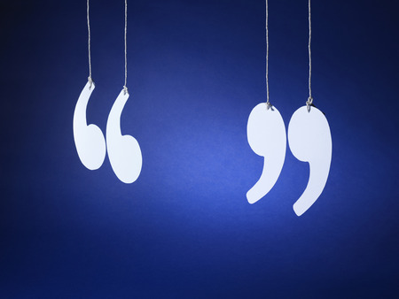 shot of quotation marks or inverted commas cut out from white card and suspended on string on a blue background Zdjęcie Seryjne