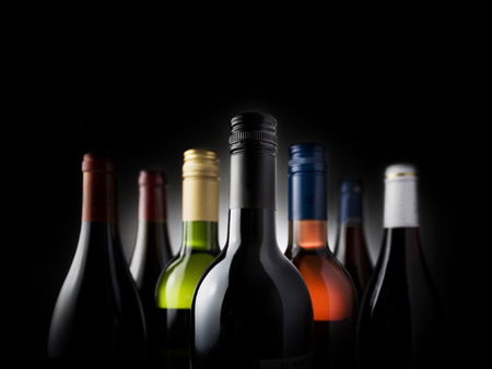group shot of seven wine bottles, backlit on black background