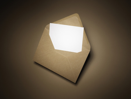 Shot of a blank piece of paper in a brown envelope, appearing to be an invite or other brief communication, with copy space for the designer to add their own message. There is a natural halo effect on the background made by lighting and not post productio