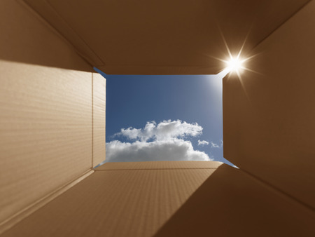 implies: Conceptual shot illustrating the phrase thinking outside the box. Implies inspirational thoughts, bright new ideas, imagination and escaping from the norm. The box has areas for copy space. Carefully positioned to show the bright blue sky and also lens